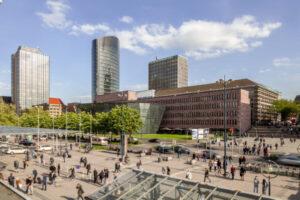 Blick auf und Stadt- und Landesbibibliothek und den Vorplatz des hauptbahnhofs Dortmund. Viele Menschen sind zu Fuß unterwegs